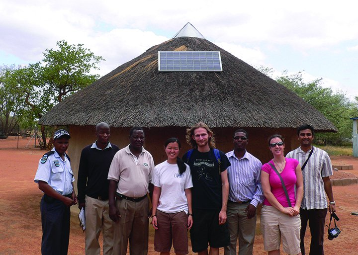 CSE students and faculty with local residents outside a traditional hut with solar panel installed